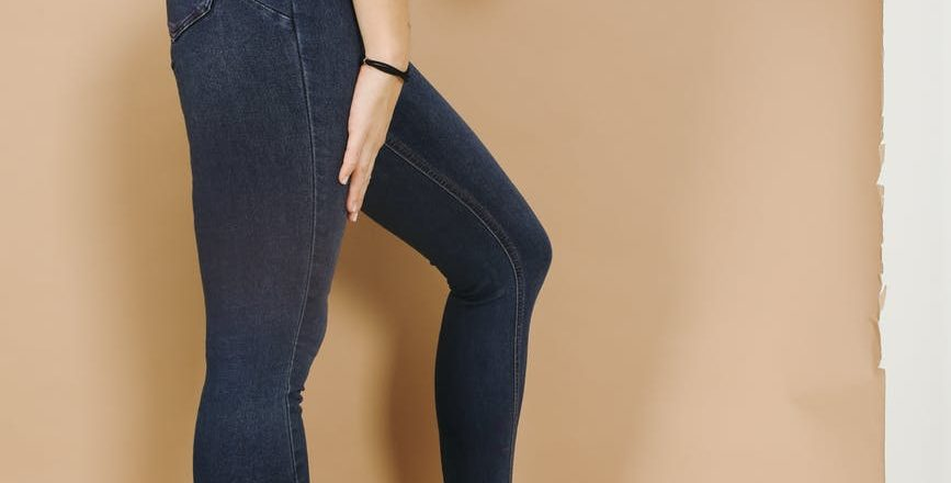 crop unrecognizable woman in jeans leaning forward on beige background